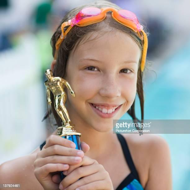 Caucasian swimmer holding swim trophy