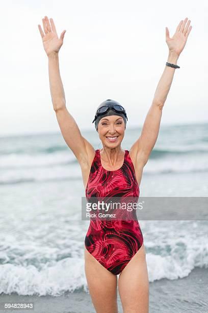 Caucasian swimmer standing on beach