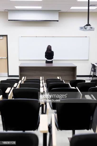 Caucasian teacher at whiteboard in empty classroom