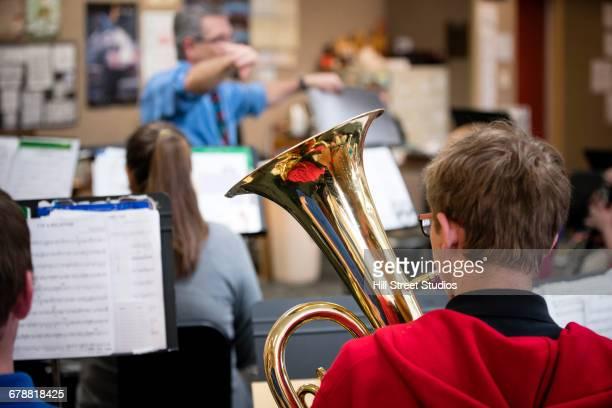 Caucasian teacher conducting students in music class