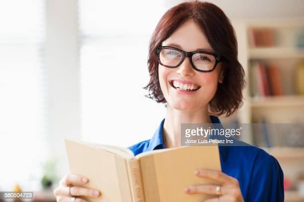 Caucasian teacher holding book in classroom