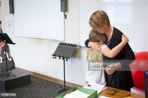Caucasian teacher hugging student in music class
