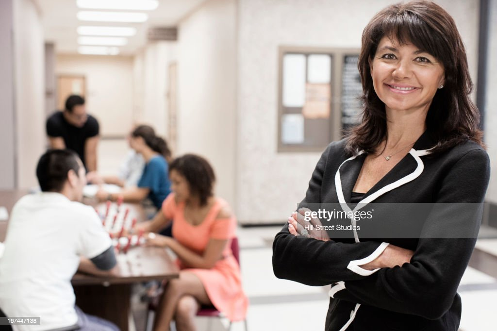 Caucasian teacher smiling in hallway : Stock Photo