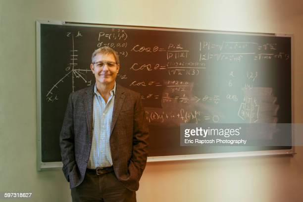 Caucasian teacher standing at chalkboard