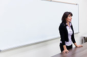 Caucasian teacher talking at whiteboard