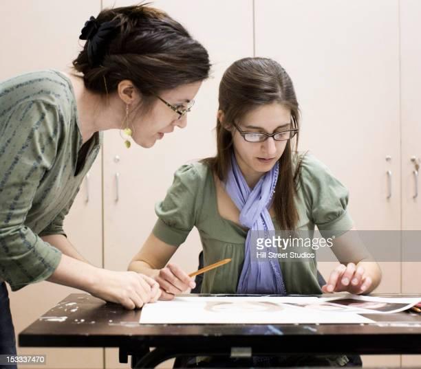 Caucasian teacher talking to student in art class