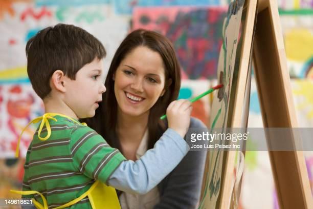 Caucasian teacher watching student painting