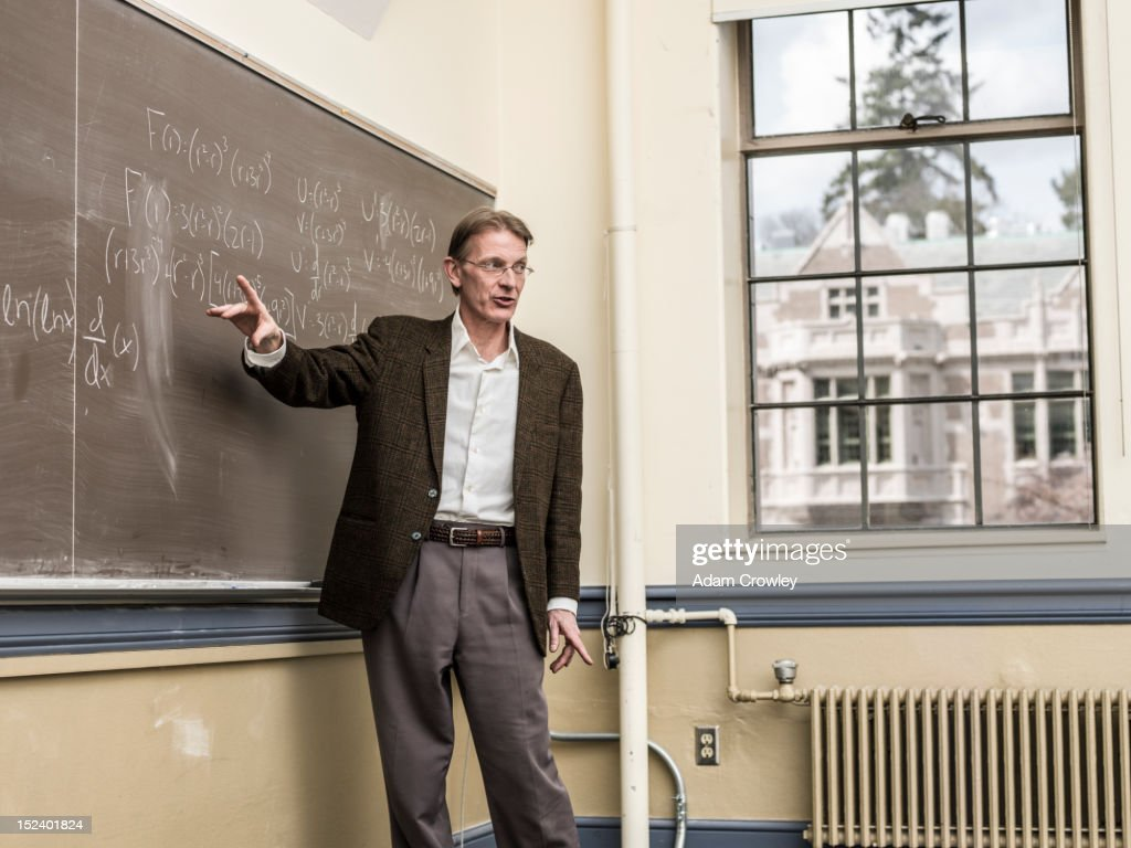 Caucasian teacher writing on blackboard : Stock Photo