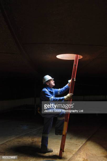 Caucasian technician climbing ladder in empty fuel storage tank