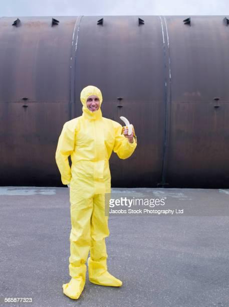 Caucasian technician in protective suit eating banana
