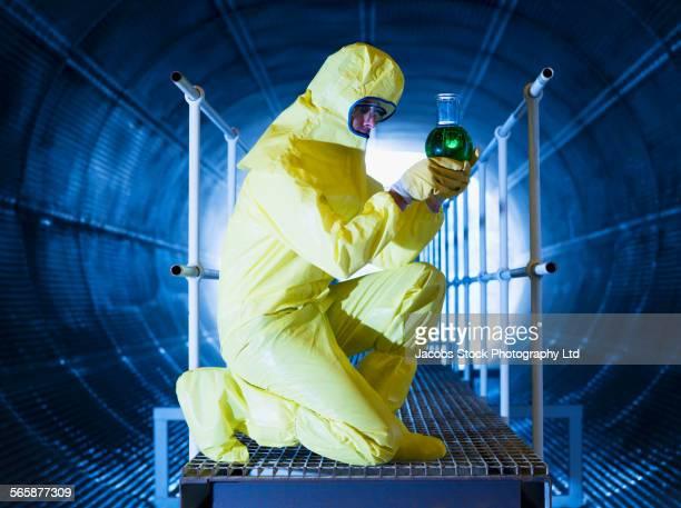 Caucasian technician in protective suit examining chemicals