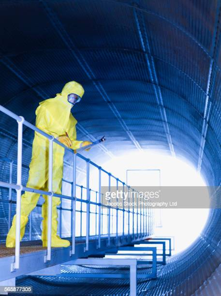 Caucasian technician in protective suit on tunnel walkway