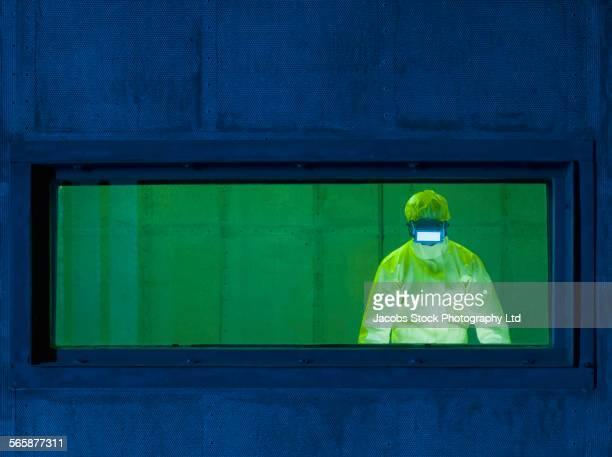 Caucasian technician in protective suit working in industrial lab