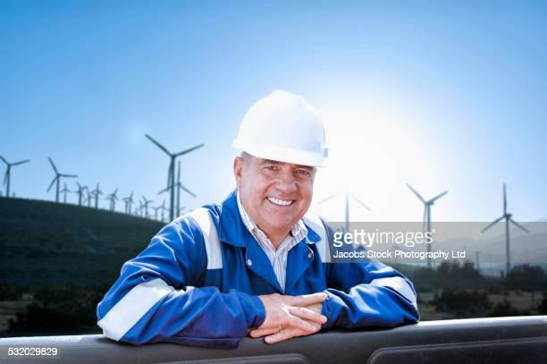 Caucasian technician smiling near field of wind turbines