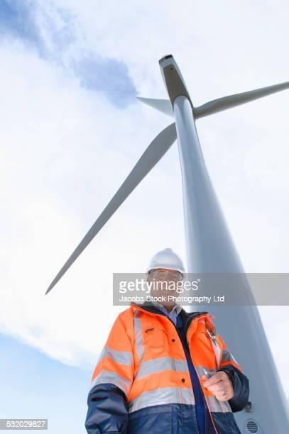 Caucasian technician smiling under wind turbine