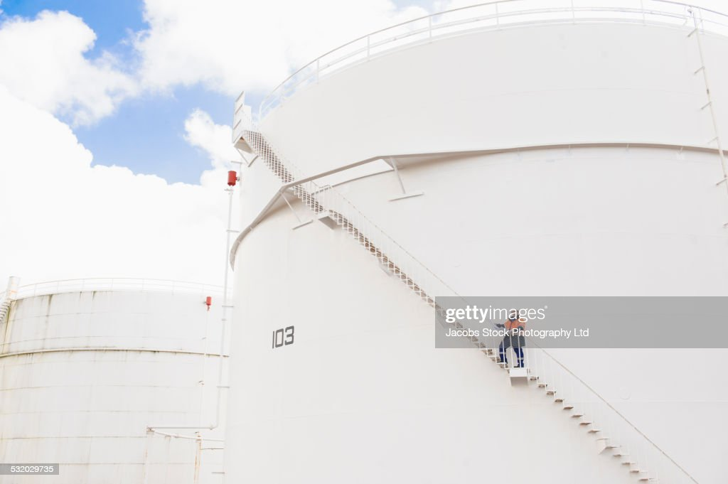 Caucasian technician standing on fuel storage tank staircase