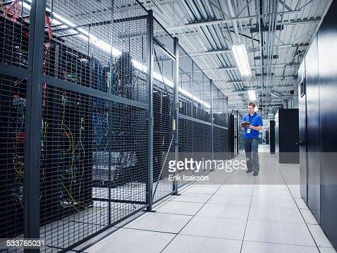 Caucasian technician using digital tablet in server room