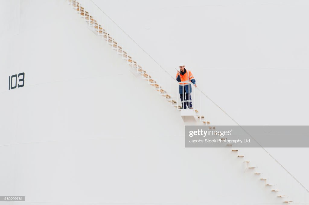 Caucasian technician using walkie-talkie on fuel storage tank staircase