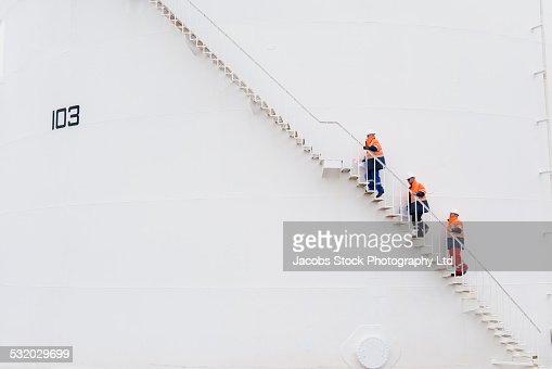 Caucasian technicians climbing fuel storage tank staircase