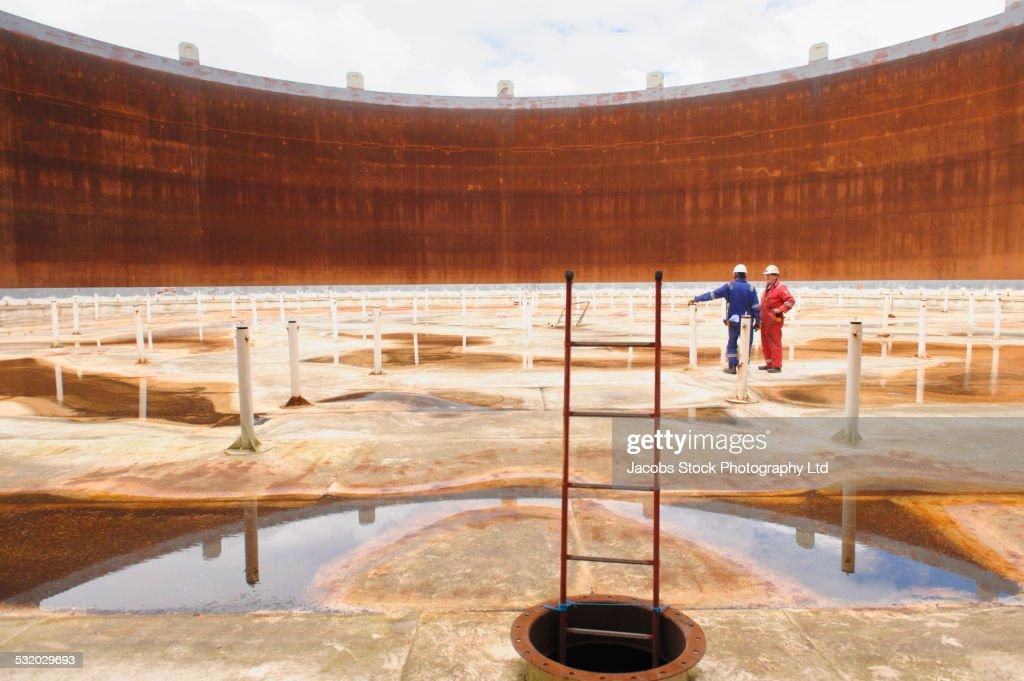 Caucasian technicians examining empty fuel storage tank