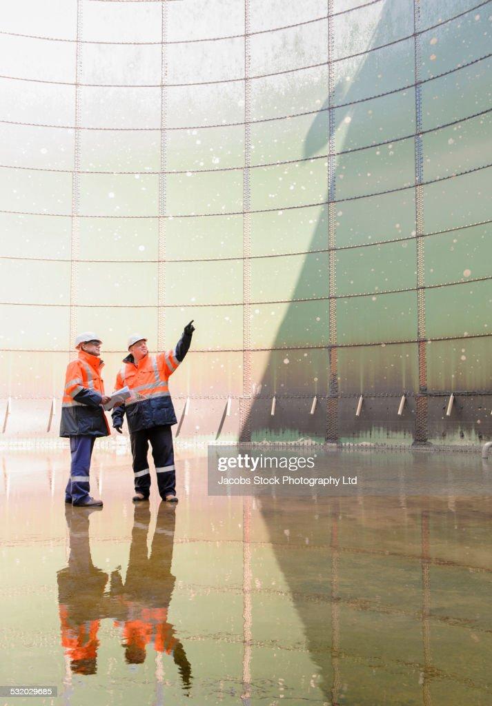 Caucasian technicians examining fuel storage tank