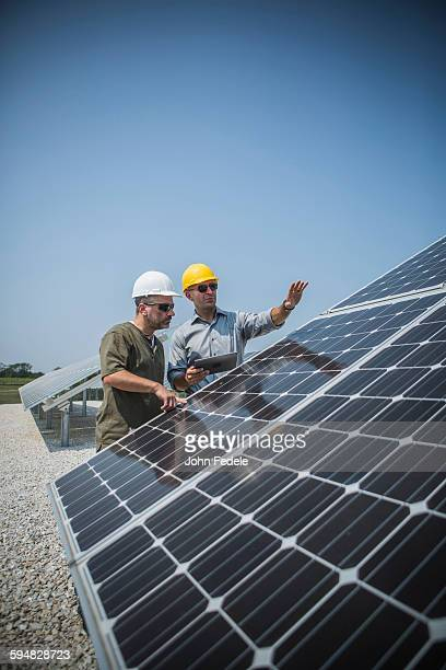 Caucasian technicians examining solar panels