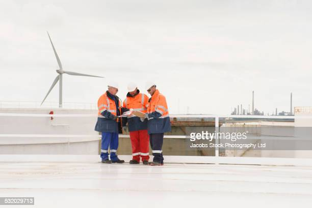 Caucasian technicians talking on fuel storage tank