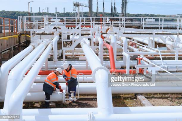Caucasian technicians tightening bolts on pipe