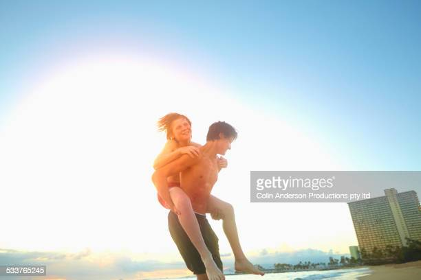 Caucasian teenage boy carrying brother on beach