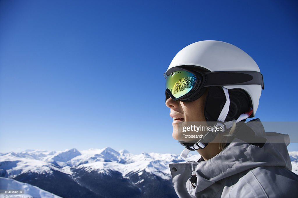 Caucasian teenage boy snowboarder wearing helmet and goggles on mountain.