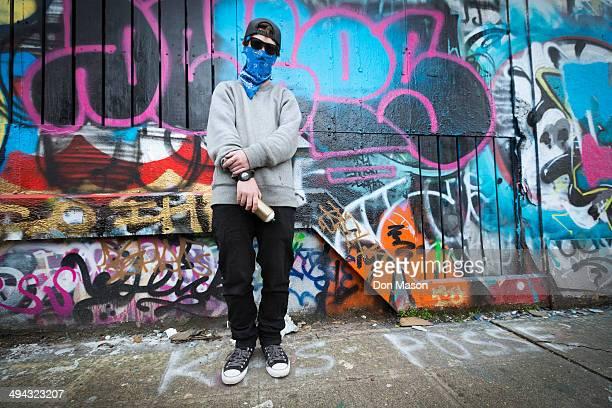 Caucasian teenage boy standing by graffiti wall