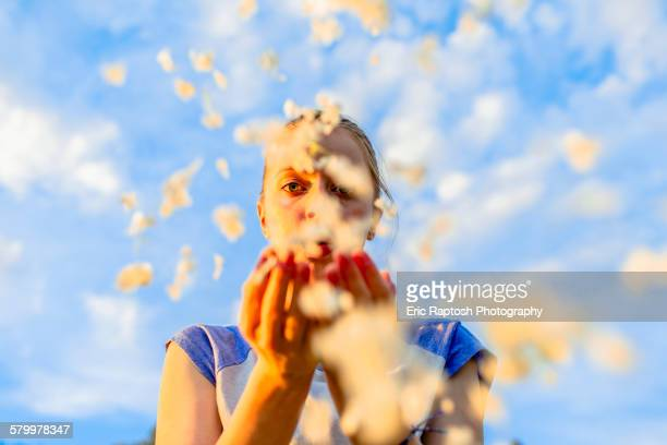 Caucasian teenage girl blowing flower petals under blue sky