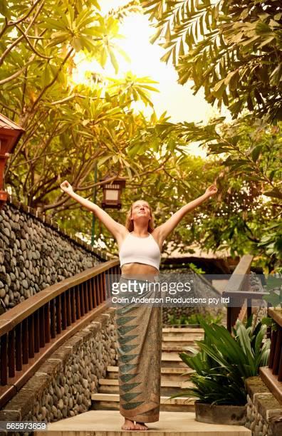 Caucasian teenage girl cheering on staircase in garden