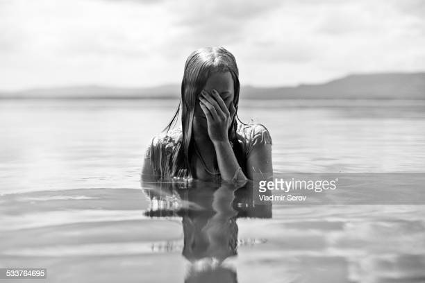 Caucasian teenage girl covering her face in lake