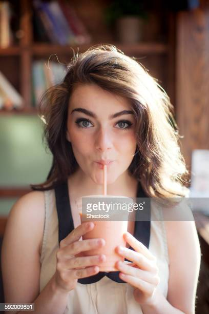 Caucasian teenage girl drinking smoothie in cafe