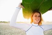 Caucasian teenage girl holding surfboard overhead on beach