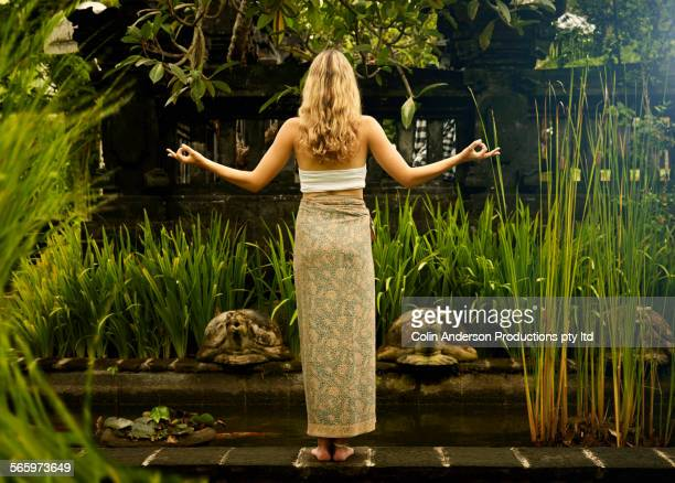 Caucasian teenage girl meditating in garden