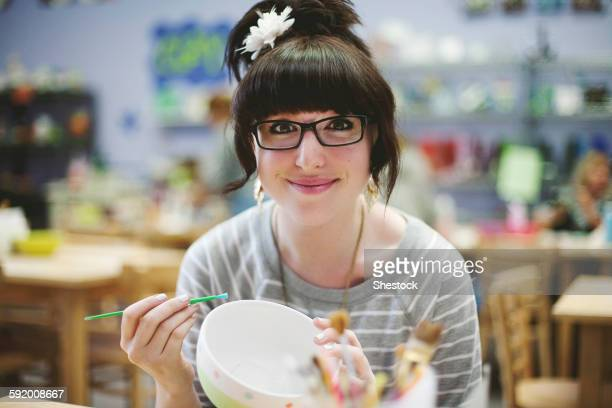Caucasian teenage girl painting pottery in class