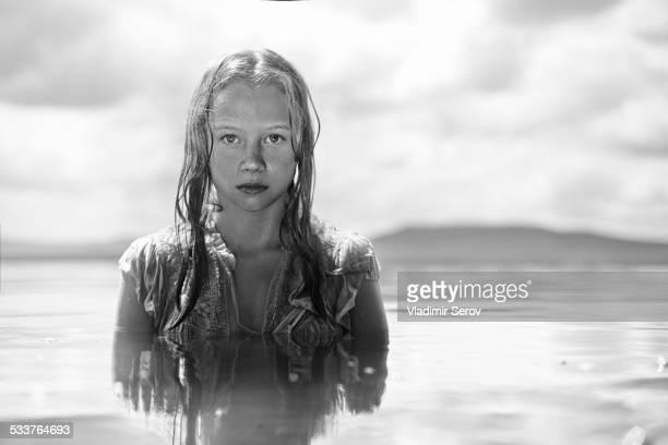 Caucasian teenage girl swimming in lake