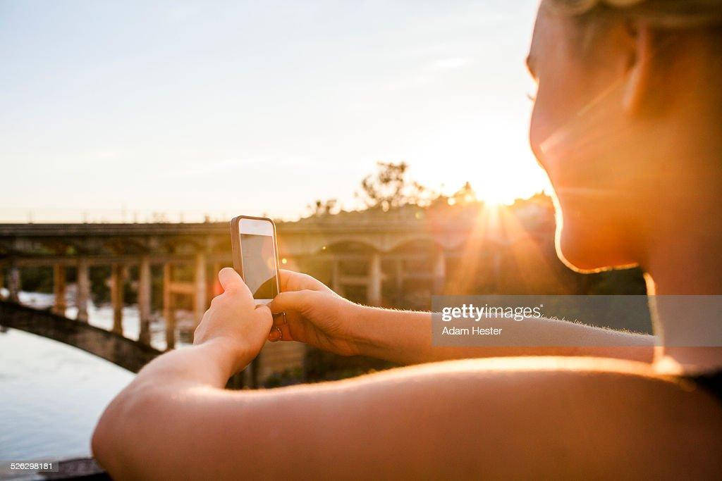 Caucasian teenage girl taking cell phone photograph of bridge