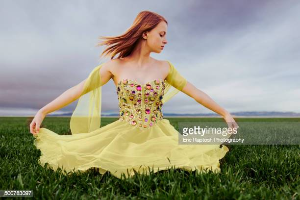 Caucasian teenage girl wearing gown in rural field