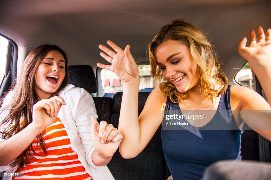 Caucasian teenage girls dancing in back seat of car