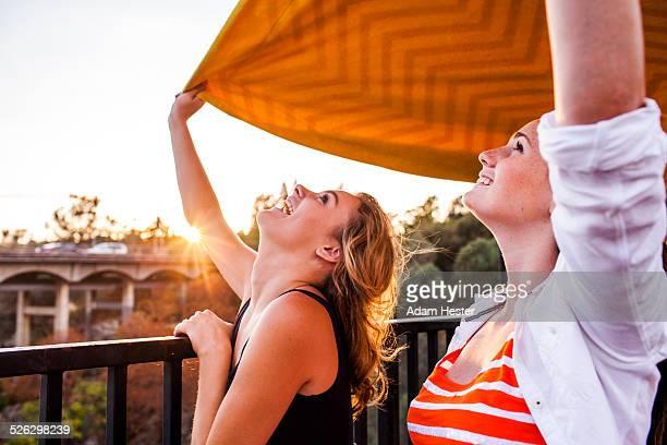 Caucasian teenage girls holding blanket on bridge