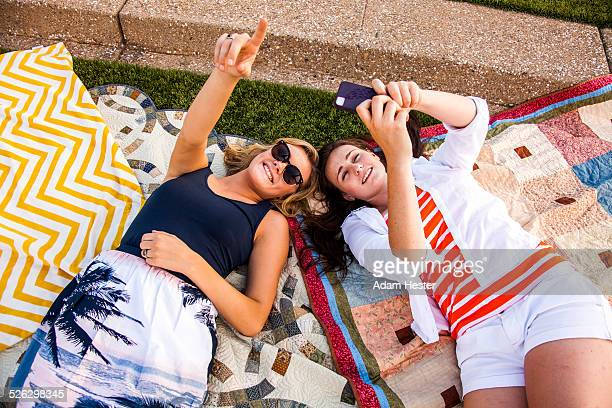 Caucasian teenage girls laying on picnic blankets in park