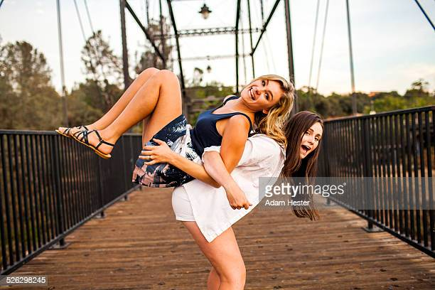 Caucasian teenage girls playing on wooden bridge