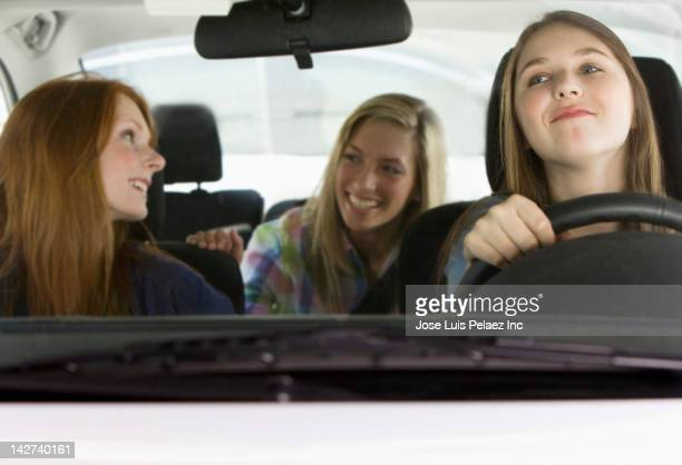 Caucasian teenage girls riding in car