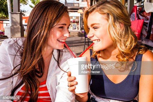 Caucasian teenage girls sharing milkshake in city