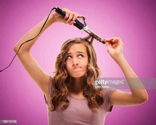 Caucasian teenager curling her hair