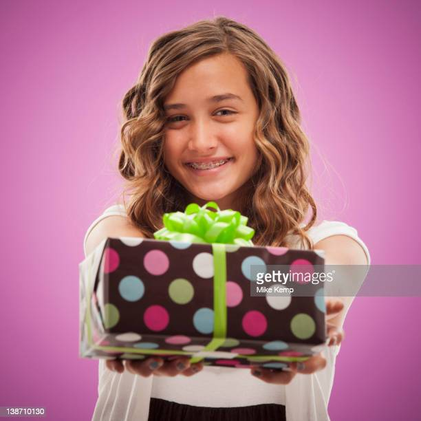 Caucasian teenager holding out gift