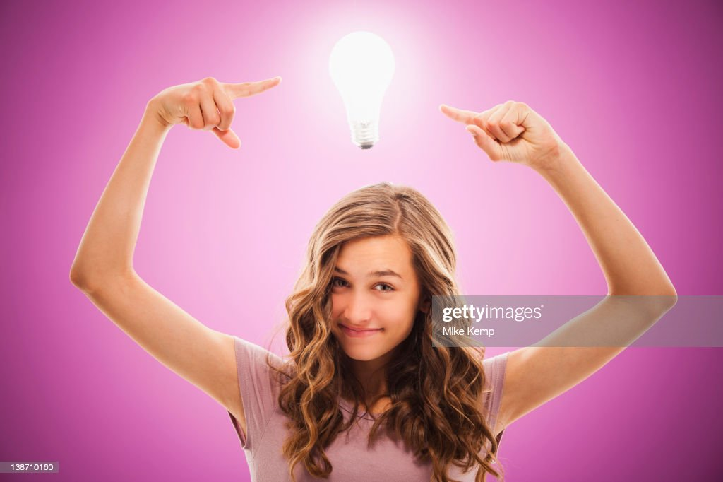 Caucasian teenager pointing at light bulb over her head : Stock Photo